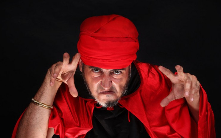 Hypnotist or sorcerer is doing hypnosis or magic with eyes and hands