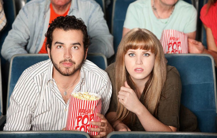 Couple with popcorn bag staring ahead in a theater