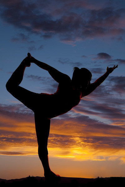 beautiful silhouette of female model in yoga pose