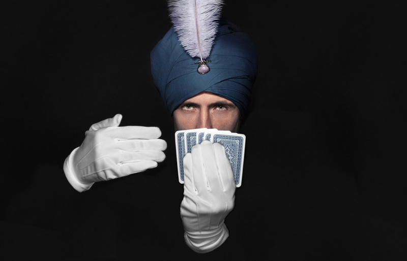 magician shows trick with cards on the dark background